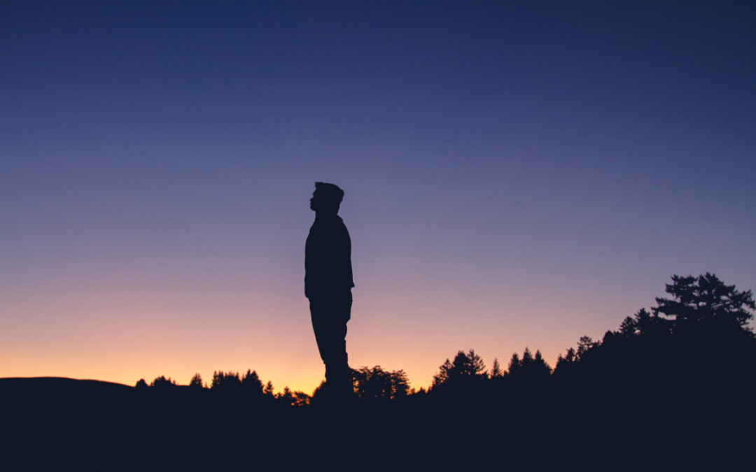 A man looks up towards the sunset sky.